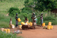 Photo of women and children         fetching water from hand pump, Sussundenga, Mozambique.