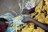 Photo of a woman making straw         mats for sale near Bukoba, Tanzania.